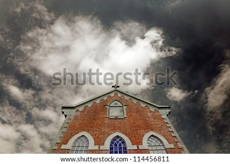 An old creepy church against an apocalyptic twilight sky for Halloween concept. - stock photo