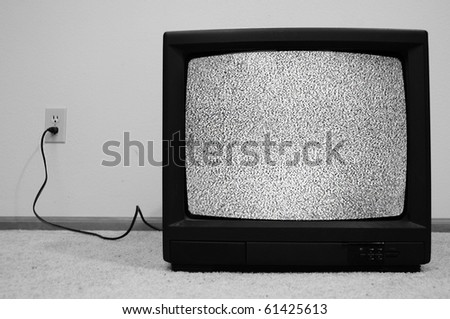 An old CRT TV plugged into the wall with static on the screen. - stock photo