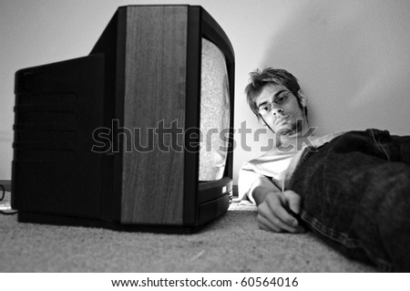 An old CRT TV plugged into the wall with static on the screen with a man watching it closely. - stock photo