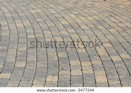 An old curved walkway made of pavers. - stock photo