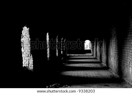 An old dark passage with the light coming from the arches - stock photo