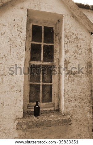an old decaying window and bottle in ireland - stock photo