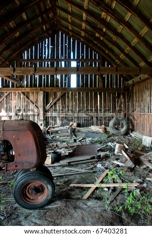 An old decrepit wooden barn full of garbage and a rusting tractor growing a plant. - stock photo