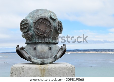 An old deep sea diving helmet, near Cannery Row in Monterey, California (USA) commemorates the divers and who installed and maintained underwater sardine pipes and pumps, including 2 who died.