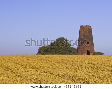 an old derelict brick windmill on the horizon of a wheat field under a deep blue sky - stock photo