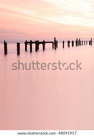 An old, derelict pier, pictured at sunrise. With space for text / editorial overlay.