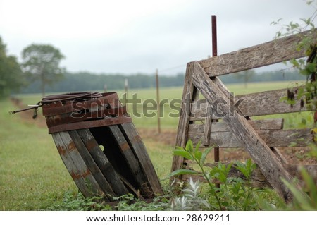 An old deteriorating wooden barrel leans away from a fence in the country. - stock photo