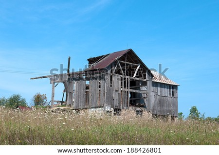 An old dilapidated wood barn in the process of falling down from neglect. - stock photo