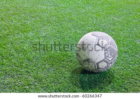 an old dirty ball on the green field - stock photo