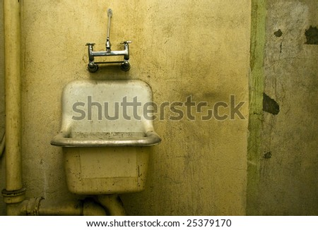 An old dirty bathroom sink in a decrepit building. - stock photo