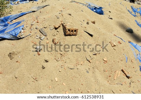 An old dirty brick laid on top of sand in construction site
