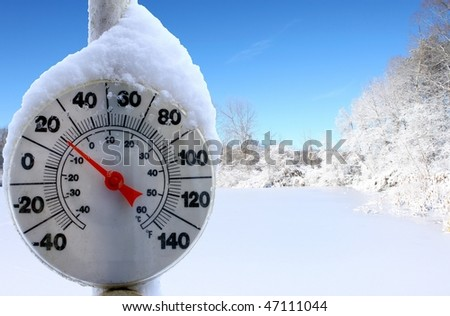 An old dirty thermometer on a pole in front of a frozen over ice skating pond showing the temperature for the skaters - stock photo