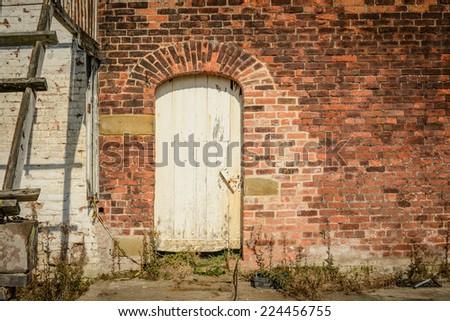 An old door set inside a Victorian garden wall - stock photo