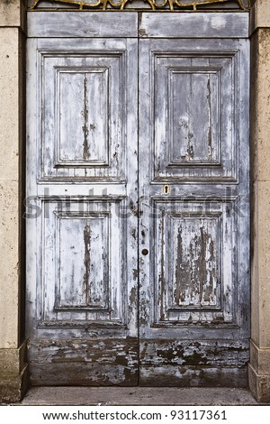 An old door with gray paint that has weathered into a remarkable texture. - stock photo