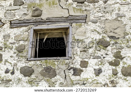 An old empty wooden window in a stone wall - stock photo