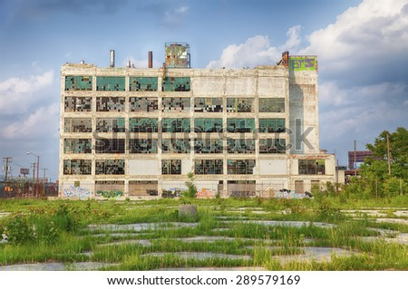 An old factory  in the Highland Park area shows the post-industrial plight of Detroit with broken windows and a parking lot filled with weeds.  - stock photo