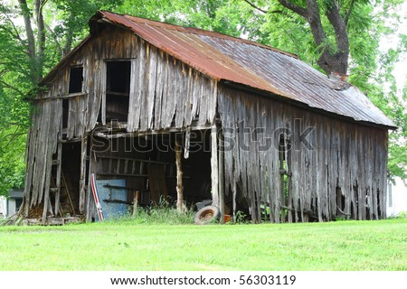 an old falling apart barn in the woods with room for your text - stock photo
