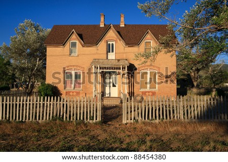 An old  farmhouse in a country setting, with a picket fence and trees around it. - stock photo
