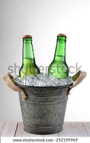 An old fashioned bucket with two beer bottles. Vertical format on a light to dark gray background with copy space.  - stock photo