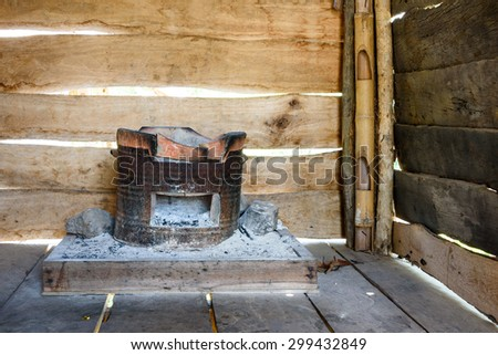 An old fashioned charcoal burning clay stove in a rustic wooden house. - stock photo