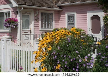 An old fashioned English style gate with bright yellow and purple flowers announces a quaint pink cottage in the background. - stock photo