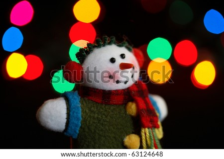 An old fashioned, hand made, snowman ornament in front of holiday lights - stock photo