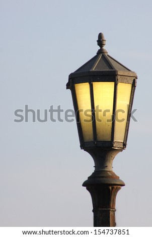 An old fashioned lit street lamp isolated against the sky at dusk - stock photo