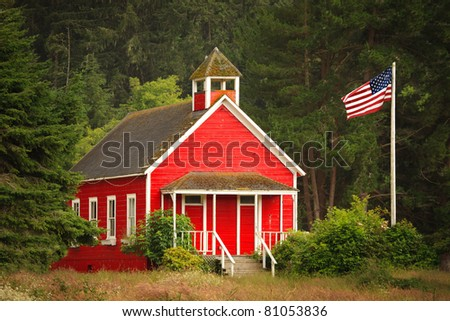 An old-fashioned little red schoolhouse in a forest area, with an American flag to the side. - stock photo
