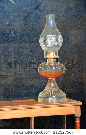 An old fashioned oil lamp is displayed in the window of an antique store.