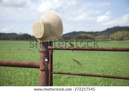 An old fashioned straw bonnet with straps blowing in the wind sits on a fence post in the Texas Hill Country - stock photo