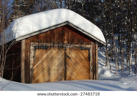 An old garage in front of the woods covered with snow