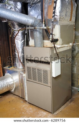 An old gas furnace in a dirty basement. - stock photo