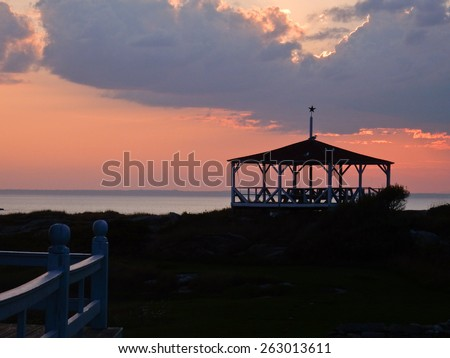 An old gazebo is silhouetted against a purple-red sunset sky. - stock photo