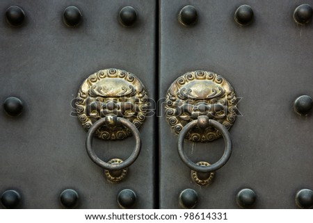 an old golden Chinese door handle on a heavy metal door - stock photo
