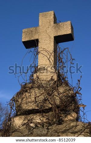 An old gravestone cross against blue sky. - stock photo