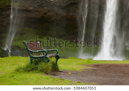An old green iron bench against a waterfall Skogafoss in Iceland