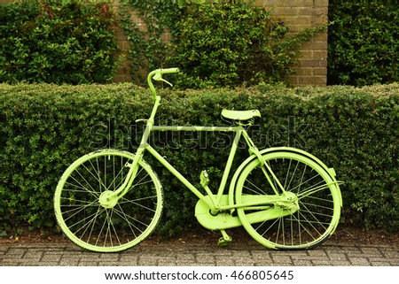 An old green painted bicycle parked against a hedge in The Netherlands.