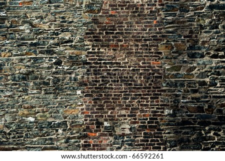 an old grey stone wall with bricks mixed into it in various colors