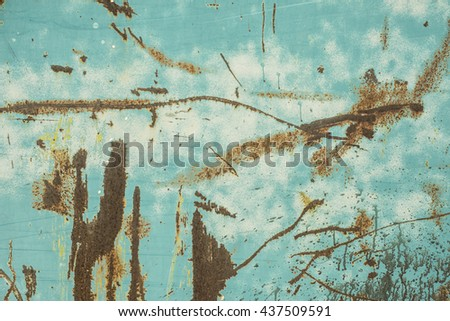 An old, grungy, turquoise metal surface with rust spots, scratches, and paint splatter. - stock photo