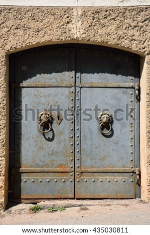 An old heavy iron door with lion motif handles. Some rust can be seen. - stock photo