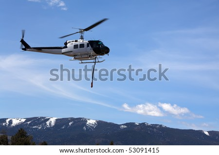 An old helicopter converted from military use to civilian fire fighting by the addition of a 360 gallon water drop tank and siphon. - stock photo