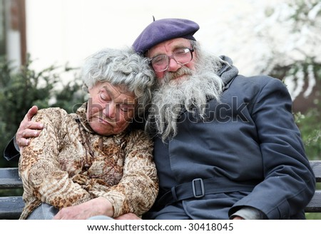 An old homeless cpuple sleeping on a bench - stock photo