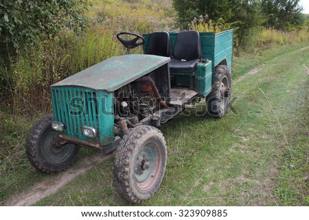 An old homemade agricultural wheel tractor in the forest
