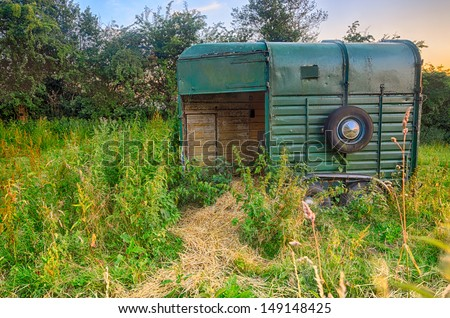 An old horse box/trailer left discarded in a field with hay to feed the horses, UK, England - stock photo