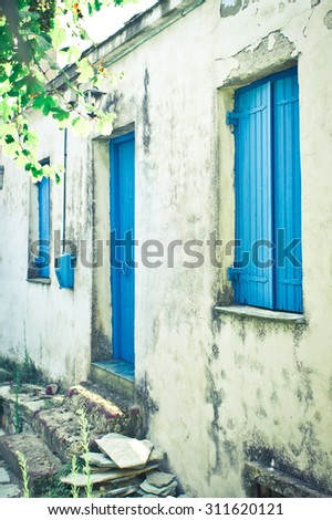 An old house in a Greek village with blue shutters and door - stock photo
