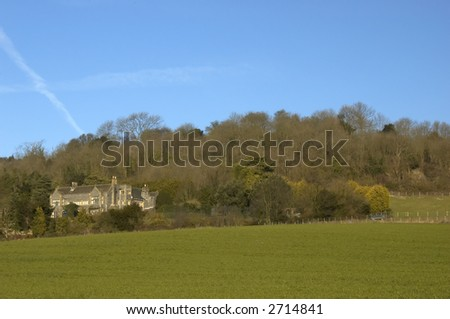 An old house on a hill with a blue sky