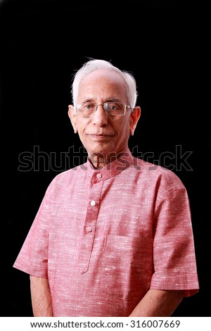 An Old Indian wearing khadi kurta , photographed and isolated against black background - stock photo