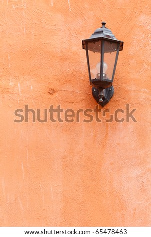 An old italian lamp isolated on orange wall - stock photo