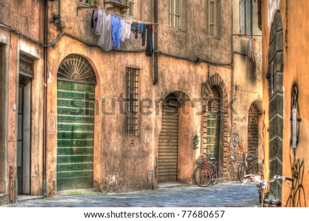 An old Italian lane with washing hanging on the line and bycicles resting in Tuscany Italy - stock photo