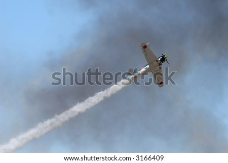 An old japanese warplane flys through heavy smoke during a simulated attack